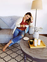 Young happy woman with cup of tea resting at home