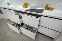 Luxurious white and black modern kitchen interior, drawers pulled out
