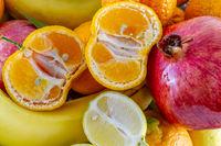 Assorted fruit arrangement of bananas, pomegranate, sliced lemon and sliced tangerine.