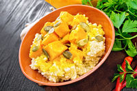 Porridge millet with spicy pumpkin in clay bowl on board