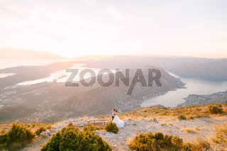 The bride and groom stand on the top of Mount Lovcen overlooking the Bay of Kotor near wooden bench, kiss and hug tenderly