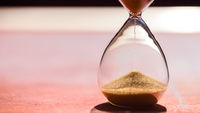 Gold Sand running through the bulbs of an hourglass measuring the passing time in a countdown to a deadline, on a light pastel reddish background with copy space