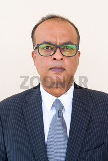 Portrait of Indian businessman wearing eyeglasses against plain wall outdoors