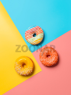 Glazed donuts on colorful background, top view