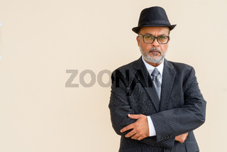 Portrait of handsome bearded Indian man wearing hat against plain wall