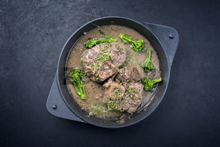 Modern style traditional braised Italian ossobuco alla Milanese with baby broccoli and herb in white wine meat sauce served in a cast-iron design skillet with copy