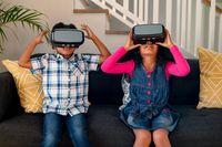 Happy african american siblings sitting on sofa, using vr headset and having fun