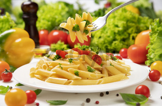 Plate of italian pasta, penne rigate on fork with tomatoes and basil