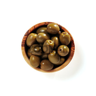 Green olives in wood bowl isolated on white