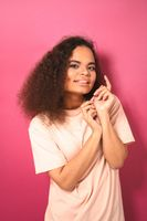 Beautiful dark skinned African American young girl looking gently at camera wearing peachy t-shirt isolated on pink background. Beauty concept. Facial expressions, emotions, feelings