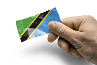 Hand holding a card with a national flag the Tanzania