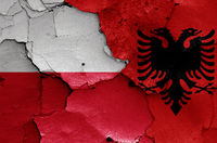 flags of Poland and Albania painted on cracked wall