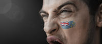 A screaming man with the image of the Tuvalu national flag on his face