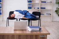Young male employee sleeping in the office on chairs