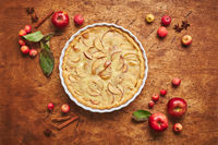 Homemade apple cake with with sour cream, red apples, Crabapples and cinnamon over wooden background, top view