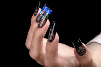 Hand with a beautiful manicure on a black background. Nail design. Extended nails.
