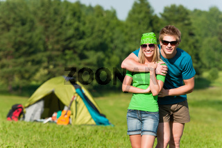 Young camping couple hugging in summer countryside