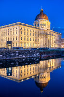 The reconstructed Berlin City Palace at night reflected in the river Spree