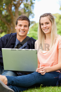 Portrait of young people laughing while sitting with a laptop