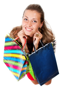 Portrait of young happy woman in dress with colorful shopping bags on a white background