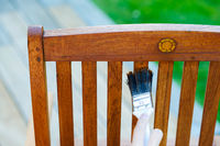 female hand holding a brush applying varnish paint on a wooden garden chair - painting and caring for wood with oil