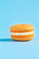 orange Cake macaron or macaroon on blue background