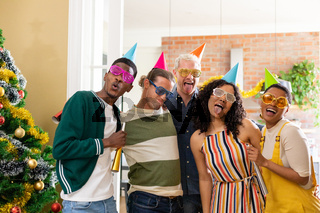 Group of happy diverse female and male friends with whistles and colorful hats celebrating new year