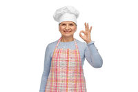 senior woman or chef in toque showing ok hand sign