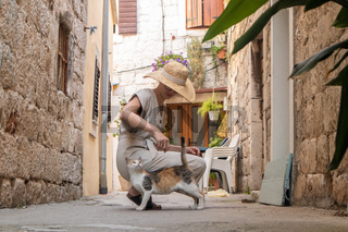 Beautiful blonde young female traveler wearing straw sun hat caressing domestic cat while enjoying summer vacation in an old traditional costal town at Adriatic cost, Croatia.