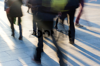 Crowd on the sidewalk at sunset with long shadows