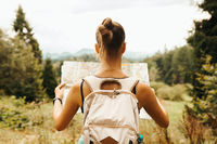 Hiking woman traveler with backpack checks map to find directions in wilderness area, real explorer.