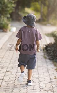 Rear view of a little cute boy walking