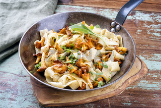 Traditional fried Italian tagliatelle con galletti with mushrooms offered as close-up in a rustic iron pan