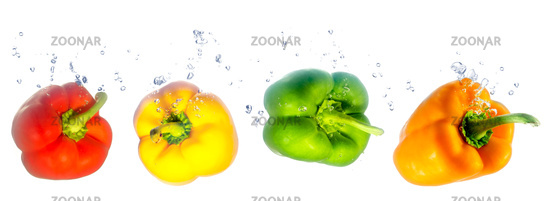 four coloured peppers fall into the water