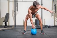 Young muscular man training with kettlebells.