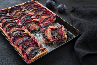 Traditional French tarte aux prunes with sweet plums and vanilla offered as closeup on a rustic metal tray