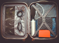 Open suitcase full of clothes isolated on black background