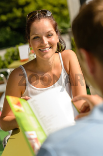 Smiling woman at restaurant terrace couple lunch