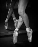 Legs of young ballerina with pointe shoes dancing on a black floor background. Ballet practice.