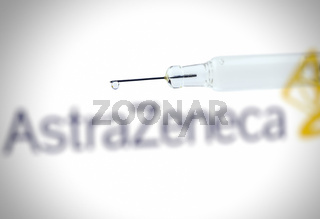 Syringe with liquid drop against the AstraZeneca logo vaccine developed in Oxford