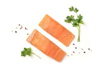 Slices of salmon with parsley and pepper, on a white background with copy space, overhead photo