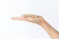 Hand holding wooden letters for health concept.