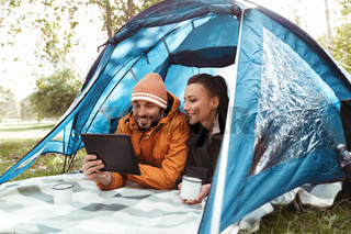 couple with tablet pc drinking tea inside tent
