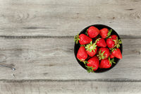 Tabletop view, small black ceramic bowl with strawberries, gray wood desk under. Space for text on left side.