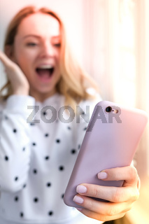 Blonde young girl taking selfie. Video call. Online education. Work from home. Woman holding smartphone. Phone call. Recording new vlog for her channel. Blogger surprised