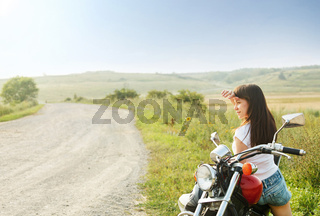 Young biker woman on the country road