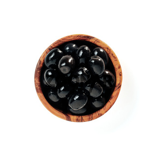 Black olives in wood bowl isolated on white