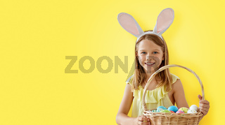 happy girl with colored easter eggs over yellow