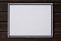 blank white sign with place for text on wooden wall
