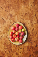 Plate with small red apples - Crabapples, on warm wooden background